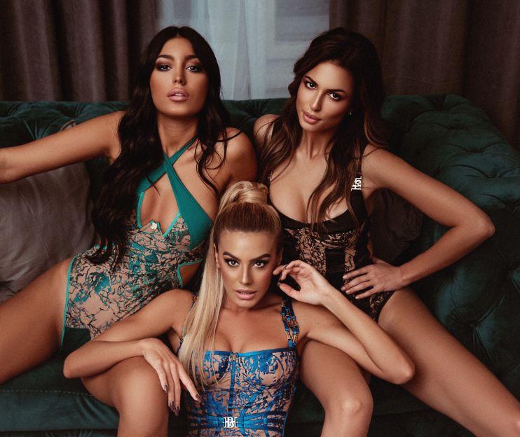 Tri ženska modela u zelenom, plavom i crnom luksuznim čipkastim korsetima na dvosedu